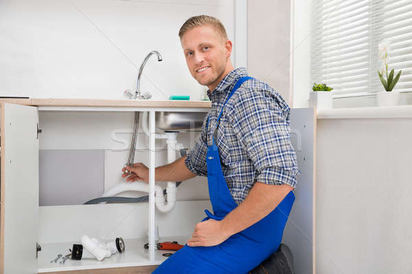 Plumber Repairing Faucet In Kitchen Stock photo © AndreyPopov