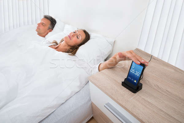 Woman On Bed Snoozing Alarm Clock On Cell Phone Stock photo © AndreyPopov