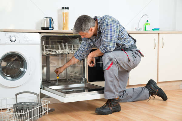 Repairman Repairing Dishwasher With Screwdriver In Kitchen Stock photo © AndreyPopov