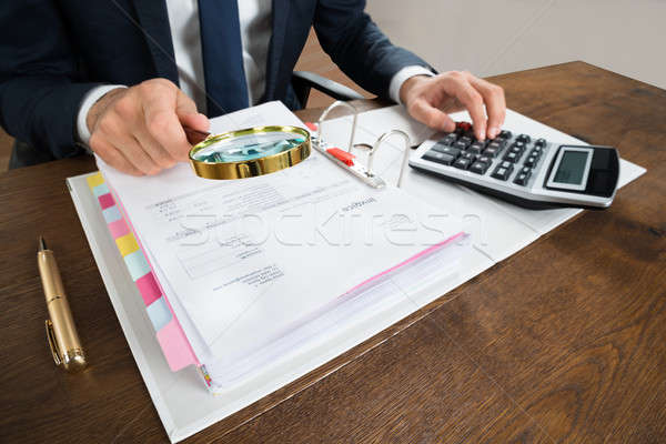 Businessman Checking Invoice With Magnifying Glass Stock photo © AndreyPopov