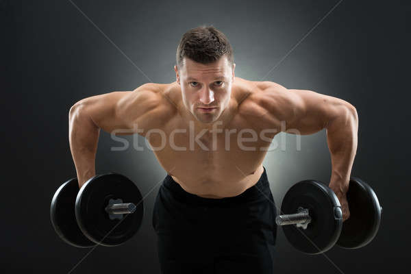 Determined Muscular Man Lifting Dumbbells Stock photo © AndreyPopov