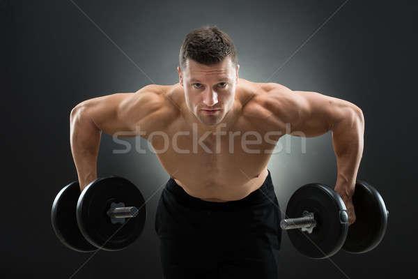 Határozott izmos férfi emel súlyzók másfelé néz Stock fotó © AndreyPopov