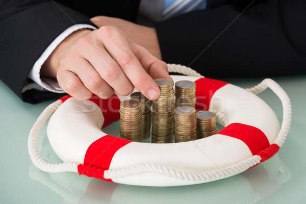 Person Holding Stack Of Coins With Lifebelt Stock photo © AndreyPopov