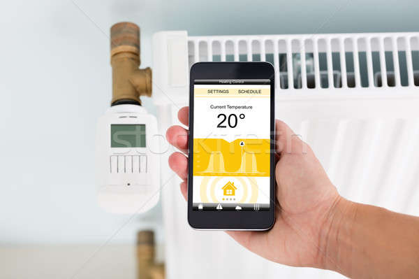 Person Adjusting Temperature Of Thermostat Using Cellphone Stock photo © AndreyPopov
