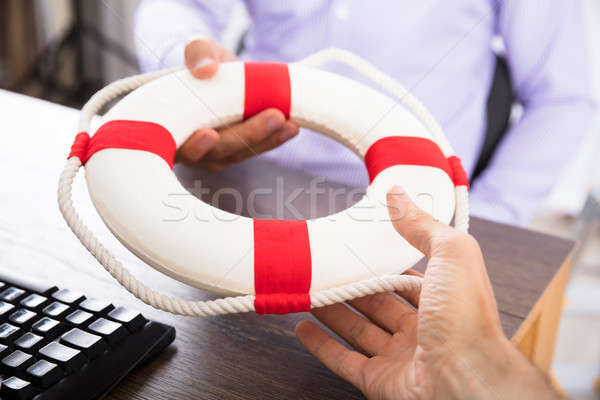 Businessman's Hand Passing A Lifebuoy To His Partner Stock photo © AndreyPopov