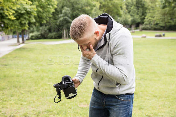 Man With Nausea Holding Virtual Reality Headset Stock photo © AndreyPopov