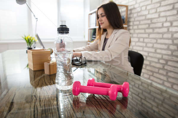Water Bottle And Pink Dumbbells On Office Desk Stock photo © AndreyPopov