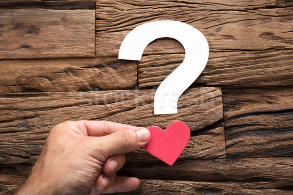 Hand Holding Question Mark With Heart On Wood Stock photo © AndreyPopov