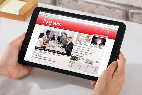 Person Holding Digital Tablet With News On Screen Stock photo © AndreyPopov