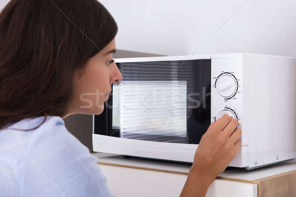 Woman Preparing Food In Microwave Oven Stock photo © AndreyPopov