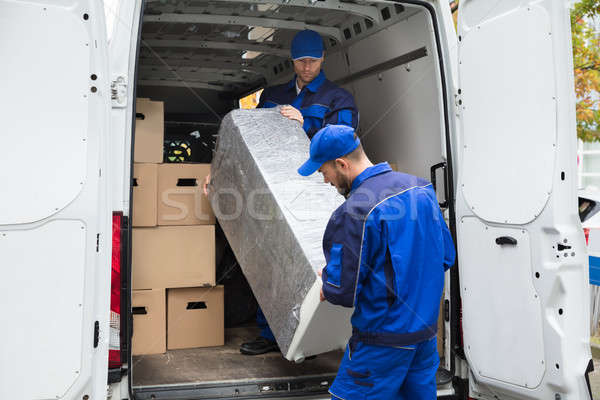Two Delivery Men Unloading Furniture From Vehicle Stock photo © AndreyPopov