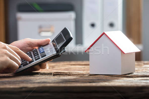 Mano humana calculadora casa modelo escritorio Foto stock © AndreyPopov