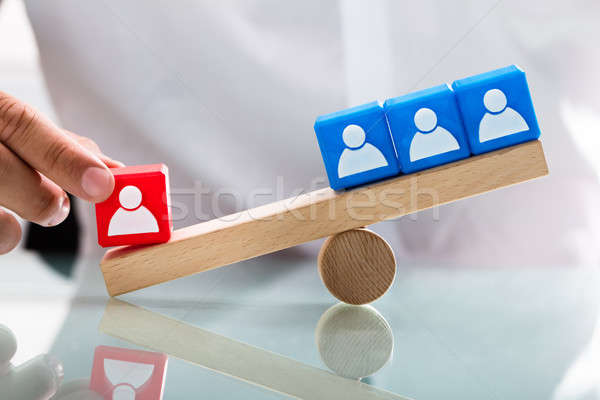 Person showing unbalance between single red and blue blocks Stock photo © AndreyPopov