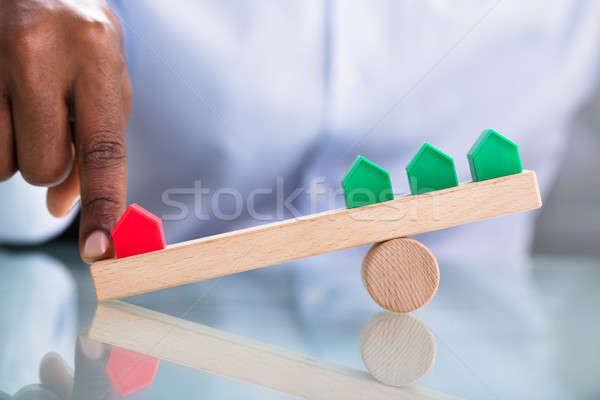 Human Hand Balancing Red And Green Miniature House Stock photo © AndreyPopov
