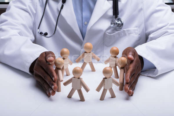 Doctor's Hand Protecting Circular Wooden Figure Stock photo © AndreyPopov