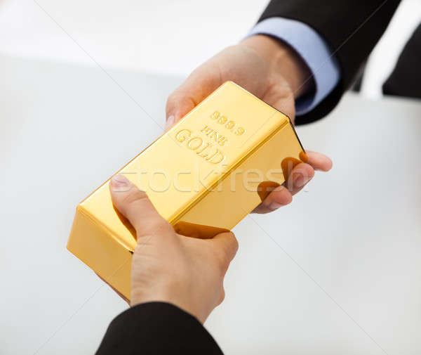 Business people exchanging golden bar Stock photo © AndreyPopov