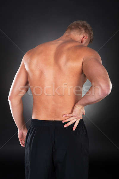 Strong muscular man with backache Stock photo © AndreyPopov