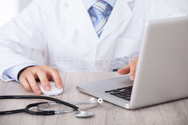 Midsection Of Doctor Using Laptop And Mouse At Desk Stock photo © AndreyPopov
