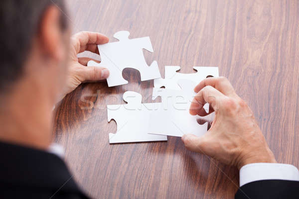 Businessman Solving Jigsaw Puzzle Stock photo © AndreyPopov