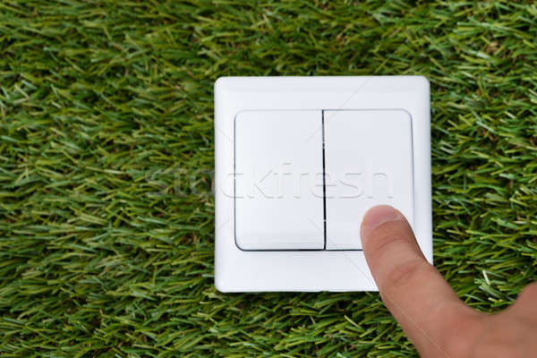 Man's Finger Pointing At Switch On Grass Stock photo © AndreyPopov