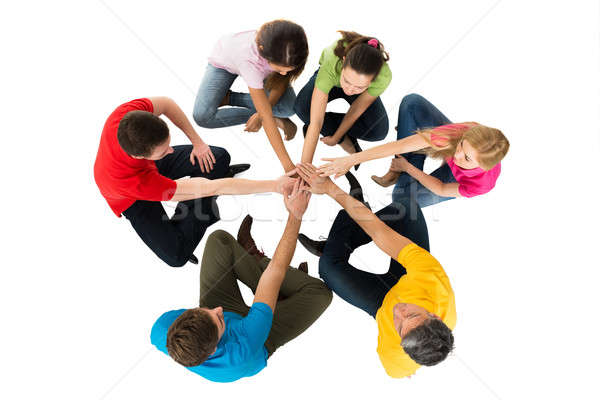 Friends Sitting In A Circle Stacking Hands Stock photo © AndreyPopov