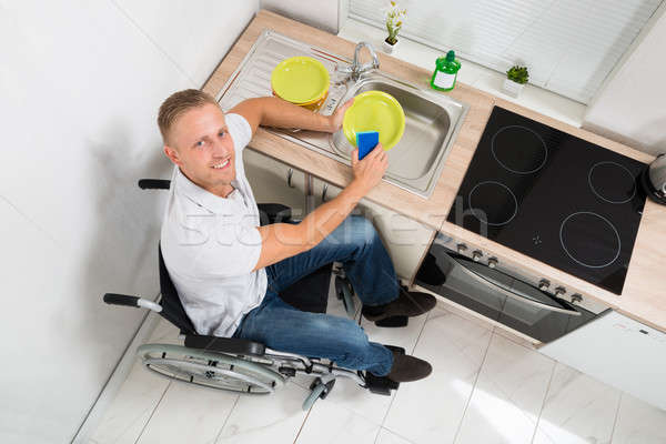 Man On Wheelchair With Sponge Washing Dishes Stock photo © AndreyPopov