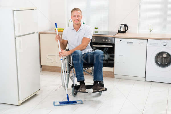 Stock photo: Handicapped Man Mopping Floor