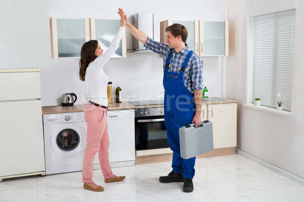 Woman Giving High Five To Repairman Stock photo © AndreyPopov
