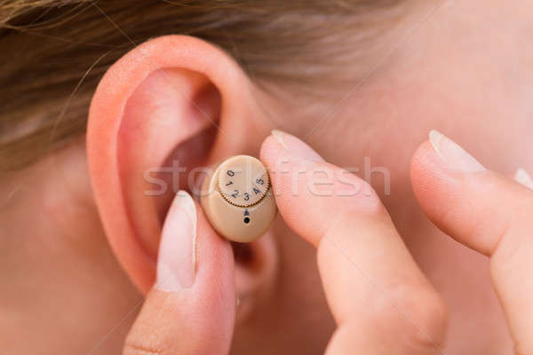 Female Hands Putting Hearing Aid In Ear Stock photo © AndreyPopov