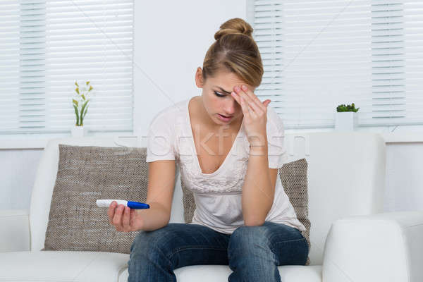 Stock photo: Woman Looking At Pregnancy Test While Sitting On Sofa