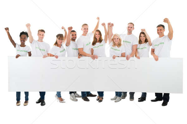 Confident Volunteers With Arms Raised Holding Blank Billboard Stock photo © AndreyPopov