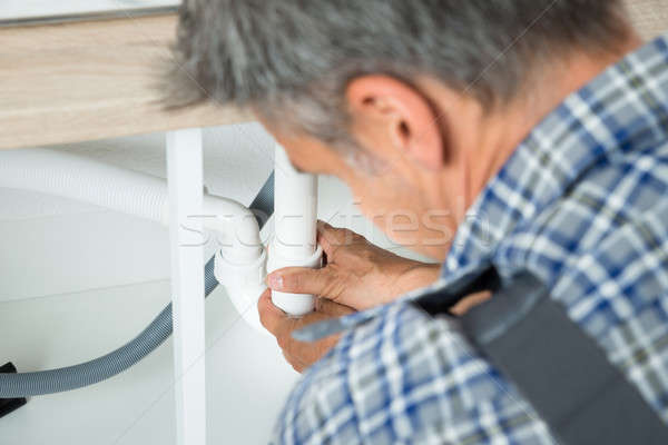 Serviceman Working On Pipes Under Kitchen Sink Stock photo © AndreyPopov