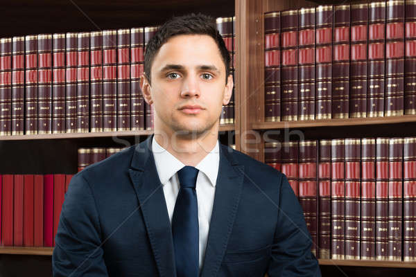 Confident Lawyer Standing Arms Crossed Against Bookshelf Stock photo © AndreyPopov