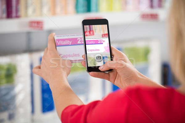 Woman Photographing Capsule Packet In Store Stock photo © AndreyPopov