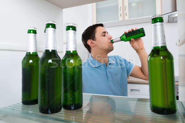 Man Drinking Beer In Front Of Refrigerator Stock photo © AndreyPopov