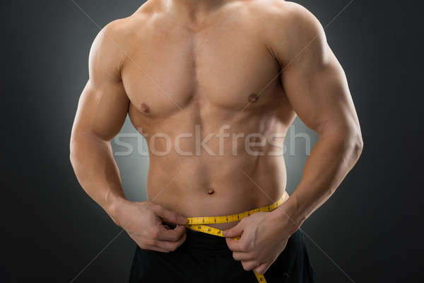 Midsection Of Muscular Man Measuring Waist Stock photo © AndreyPopov