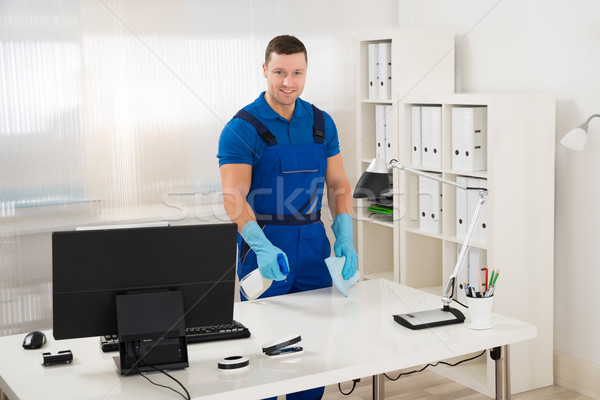 Worker Cleaning Computer Desk With Spray And Sponge Stock photo © AndreyPopov