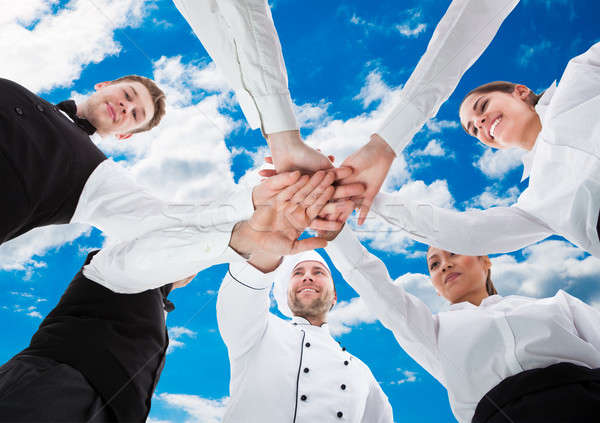 Waiters And Waitresses Stacking Hands Against Sky Stock photo © AndreyPopov