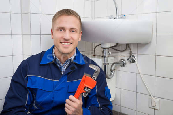 Plumber Holding Wrench Sitting Next To Sink Stock photo © AndreyPopov