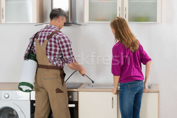 Worker Spraying Insecticide In Kitchen Stock photo © AndreyPopov