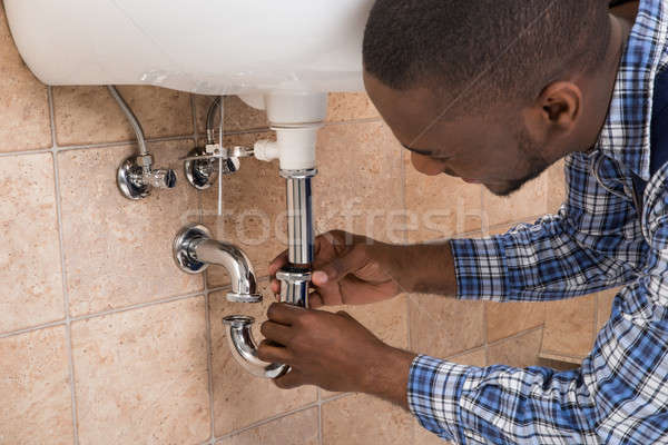 Plumber's Hand Fixing Sink In Bathroom Stock photo © AndreyPopov