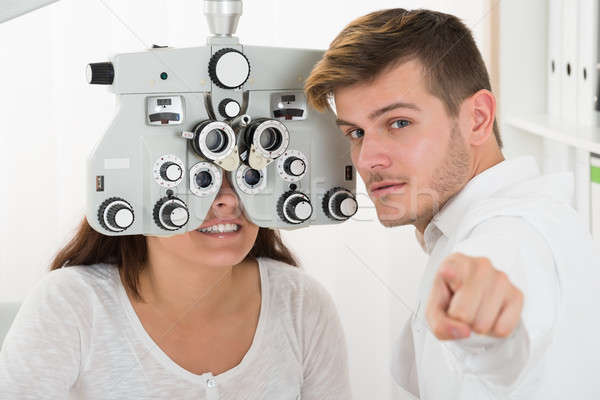 Woman Looking At Eye Test Machine In Ophthalmologist Stock photo © AndreyPopov