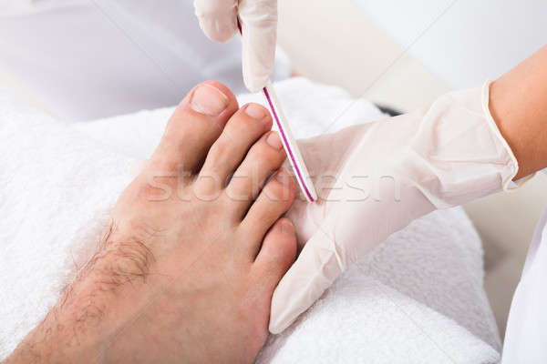Beautician Hand Filling Person's Nail Stock photo © AndreyPopov