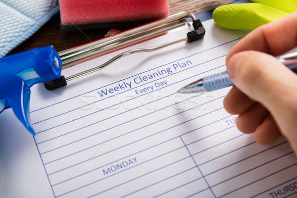 Person Hand Filling Weekly Cleaning Plan Form Stock photo © AndreyPopov