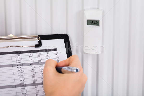 Person Hand With Clipboard Checking Digital Thermostat Stock photo © AndreyPopov