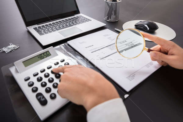 Businesswoman Looking Invoice Through Magnifying Glass Stock photo © AndreyPopov