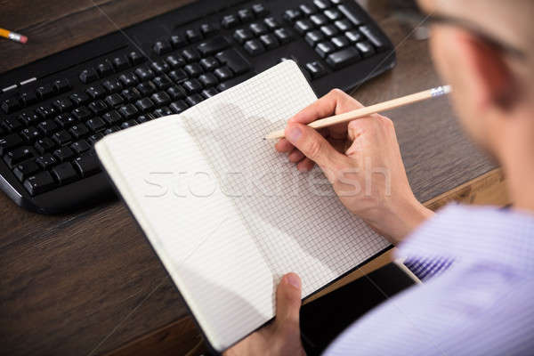 Businessman Writing Down In Checkered Notebook Stock photo © AndreyPopov