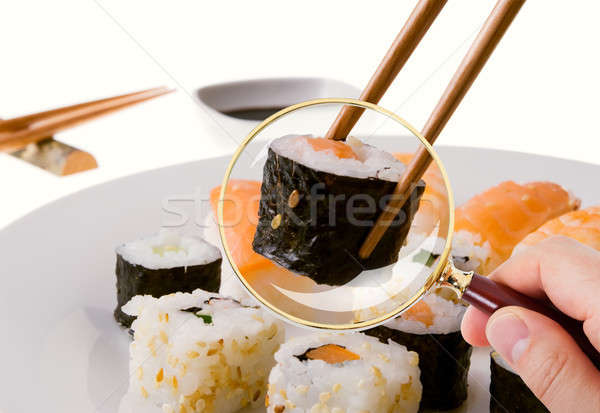 Hand Scrutinizing Sushi Served In Plate Through Magnifying Glass Stock photo © AndreyPopov