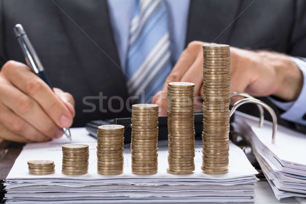 Businessman Calculating Invoice With Stacked Coins Stock photo © AndreyPopov
