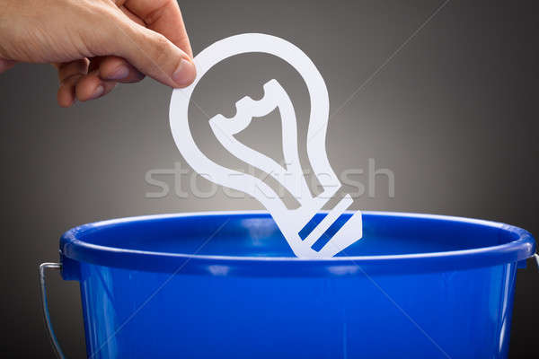 Businessman Throwing Paper Light Bulb In Blue Bucket Stock photo © AndreyPopov